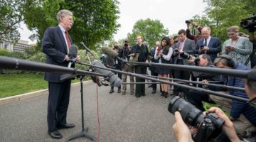 John Bolton stands in front of numerous microphones and reporters