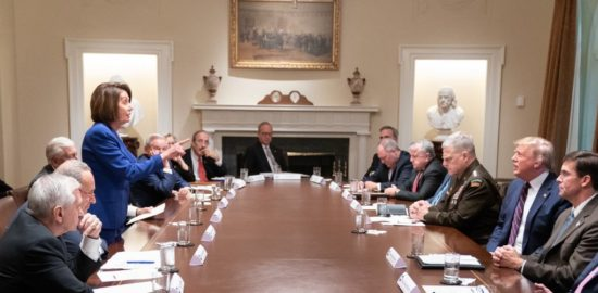 Nancy Pelosi, talking and pointing her finger, stands across the table from Donald Trump, also talking.