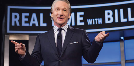 Comedian Bill Maher stands on his set with show graphics behind him.