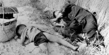 A black and white photo with adead child and a dead woman lying diagonally in a trench in the My Lai massacre